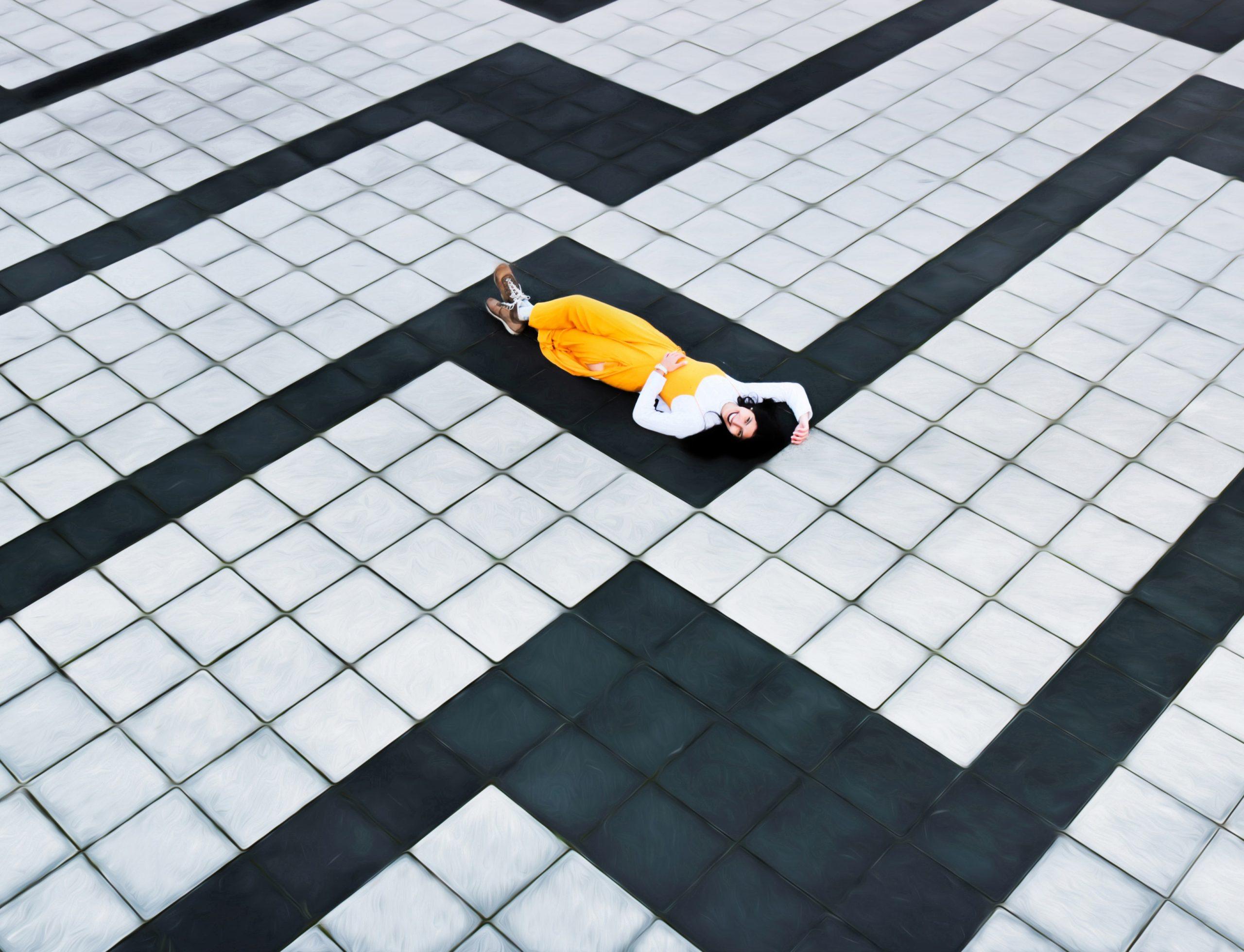 woman in yellow pants lying on tiled floor
